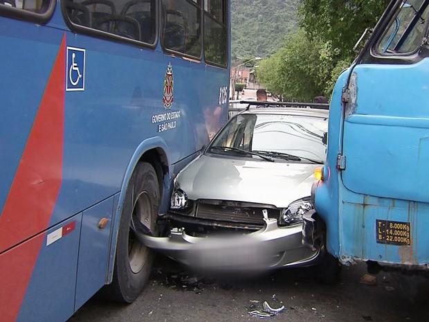 Carro foi prensado entre um ônibus e um caminhão no litoral de SP (Foto: Reprodução/TV Tribuna)
