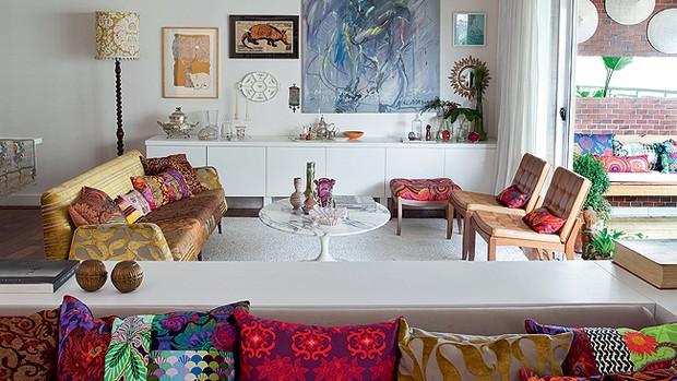 Na sala de estar, sofá estilo anos 1950 com patchwork de Ana Morelli, executado pela tapeceira Lilian Capotorto. À esquerda do bufê, fabricado pela Magal Marcenaria, o abajur de madeira torneada é herança de família. Na parede, obra de Celso Orsini. Sobr (Foto: Lufe Gomes)