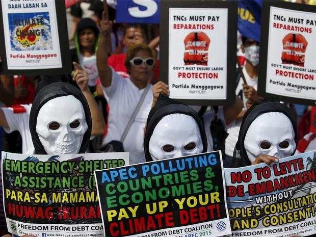 Ativistas filipinos usam máscaras de caveira durante protesto contra o aquecimento global em Quezon, na região metropolitana de Manila, neste sábado (28) (Foto: Erik De Castro/Reuters)