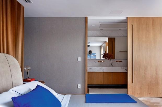 Passagem Uma grande porta de correr de tauari dá privacidade ao banheiro dos proprietários (Foto: Denilson Machado / MCA Estúdio)
