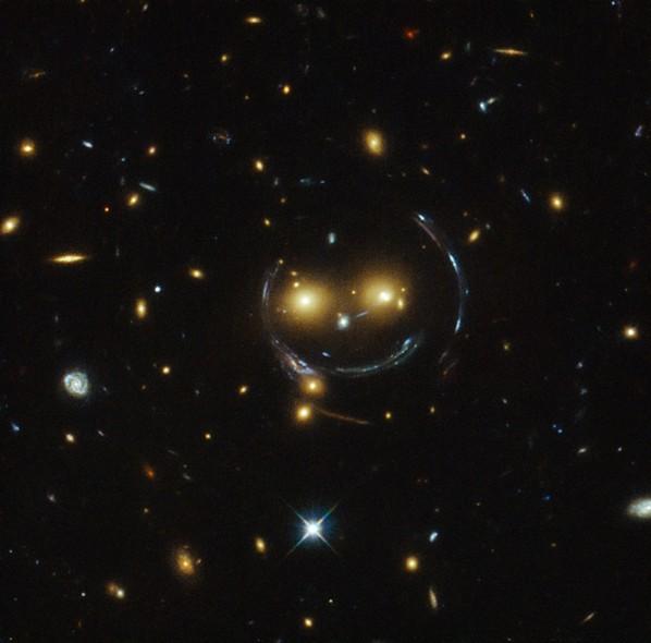 25 anos do Telescópio Espacial Hubble: O aglomerado de galáxias SDSS J1038+4849. O efeito de lente gravitacional faz com que o aglomerado se pareça com um rosto sorrindo