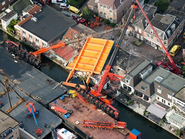 Foto aérea mostra guindastes e pedaço de ponte que caíram sobre uma fileira de casas em Alphen aan den Rijn, na Holanda, na segunda (3) (Foto: AFP Photo/ANP/Bram Van De Biezen)