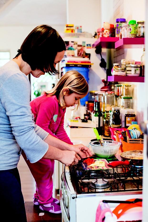 Chlóe, de 4 anos, ajuda a mãe na cozinha. Para alcançar a pia, ela sobe em um banquinho (Foto: Guilherme Zauith/Editora Globo)