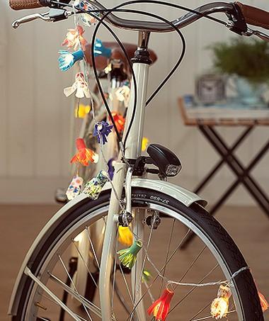 """Feitas de feltro, com uma """"franja"""" recortada, as florzinhas envolvem as lâmpadas e transformam até a bike em item de decoração. Bicicleta Trousseau (Foto: Cacá Bratke/Editora Globo)"""