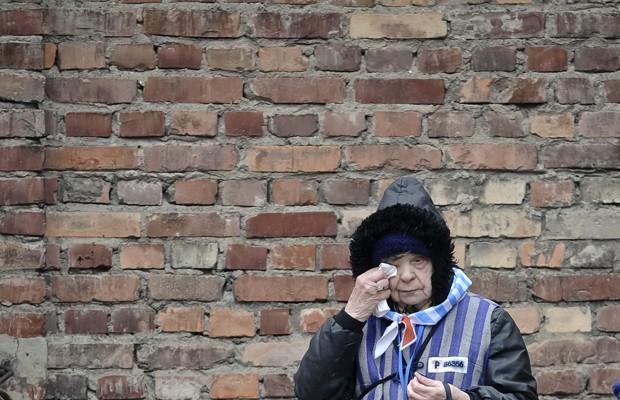 Sobrevivente chora em visita a edifício de detenção de Auschwitz, nesta terça (27) (Foto: Alik Keplicz/AP)