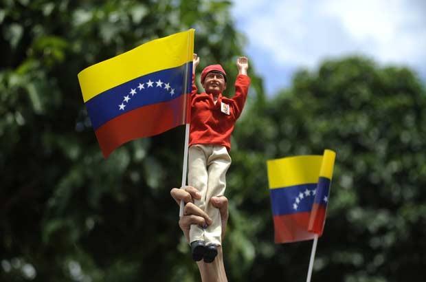 Partidário de Chávez levanta boneco do presidente durante o período de votação nesta segunda-feira (8) (Foto: AP)