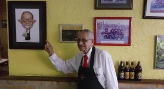 Álvaro de Oliveira, garçom do bar, ao lado de sua caricatura (Foto: Emílio Botta)