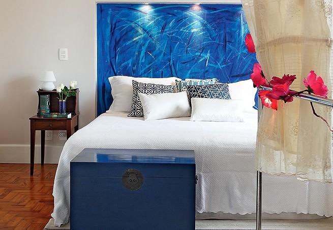 Ainda no apê da designer Carol Ferreira, outra vez o recurso do baú: aqui, ele aparece em versão de madeira, pintado de azul. Ao pé da cama, pode ser usado para guardar toalhas e lençóis (Foto: Evelyn Müller/Editora Globo)