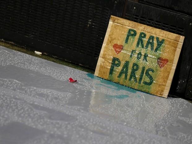Cartaz pedindo orações por Paris solta tinta sob a chuva durante vigília à luz de velas em solidariedade ao povo francês organizada em Sydney, na Austrália