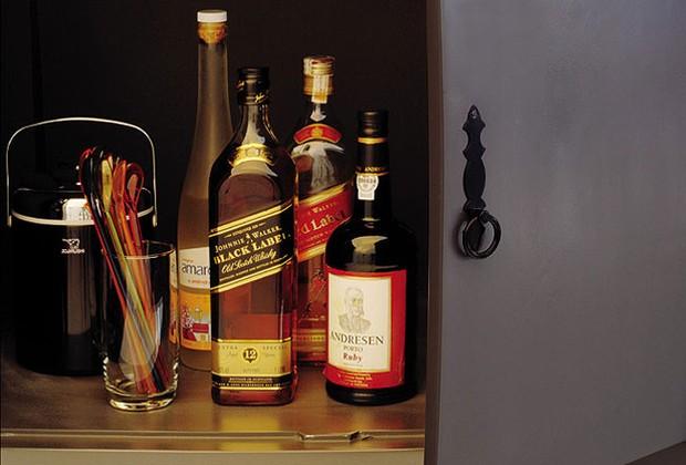 Dentro da cômoda são guardadas as garrafas fechadas, o balde de gelo e outros acessórios do bar. Também de estilo antigo, o fecho é de ferro escurecido, comprado em loja da rua do Gasômetro (Foto: Casa e Jardim)