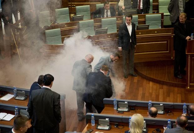 Parlamentares tentam fugir de gás lacrimogêneo lançado no Parlamento do Kosovo nesta quinta-feira (15) (Foto: Visar Kryeziu/AP)