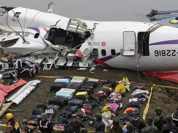 Bagagens que eram levadas no voo GE235 da TransAsia caído na véspera em um rio de Taipei, em Taiwan, são reunidas em frente à carcaça destruída do avião (Foto: Pichi Chuang/Reuters)