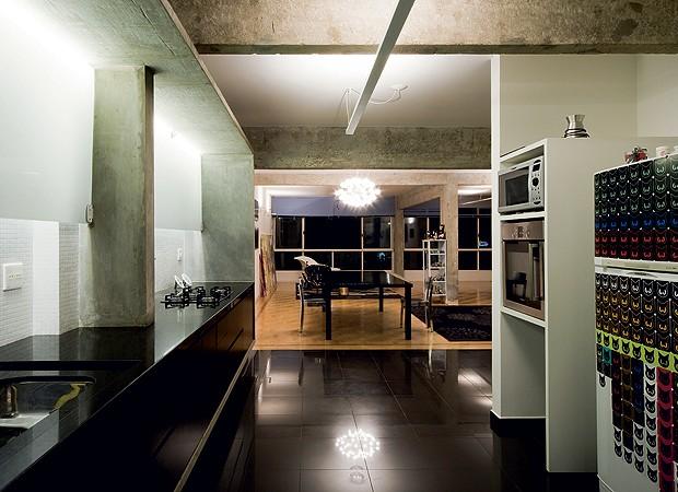 Abaixo das vigas de concreto aparente na cozinha, o arquiteto criou a caixa de mesmo material para instalar a bancada de granito preto, com armário da mesma cor. A janela foi escondida pelo vidro serigrafado com iluminação embutida, que, à noite, vira uma (Foto: Maíra Acayaba)