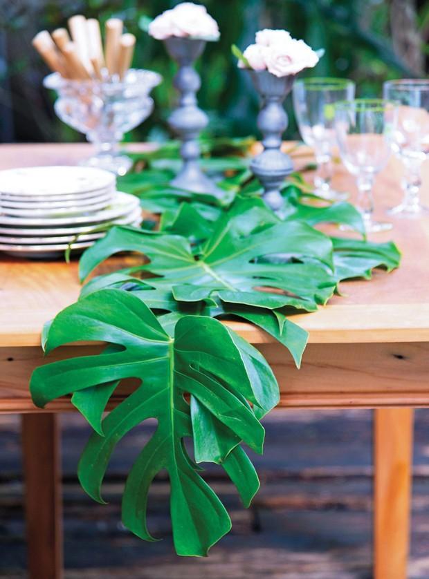 Folhas de costela-de-adão formam um caminho de mesa todo verde. Mesa Via Vila, copos Tania Bulhões, vasos D. Filipa e K&D Ideias Legais (Foto: Cacá Bratke / Editora Globo)