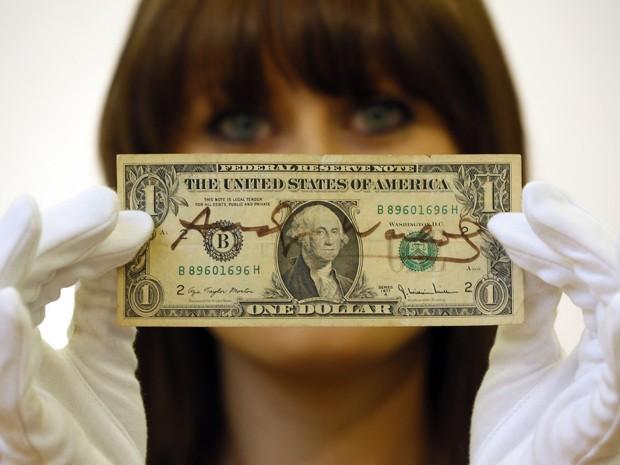 Nota de 1 dólar autografrada pelo artista Andy Warhol foi colocada em leilão na casa Christie's, no Reino Unido (Foto: Kirsty Wigglesworth/AP)