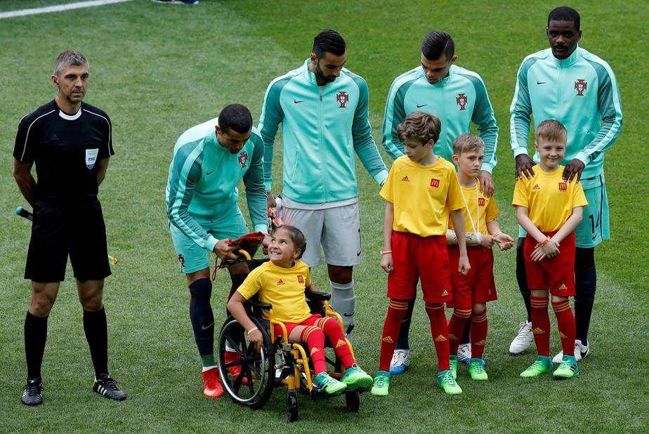 Cristiano Ronaldo presenteia mascote cadeirante com casaco