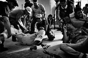 Rebelde ferido em troca de tiros é socorrido por companheiros (Foto: Mauricio Lima)