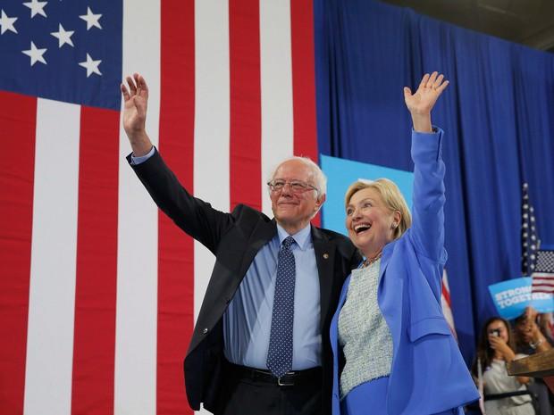 A candidata do partido democrata Hillary Clinton e o senador Bernie Sanders acenam durante um comício de campanha em Portsmouth, nos EUA, onde Sanders declarou apoio à Clinton nas eleições presidenciais (Foto: Brian Snyder/Reuters)