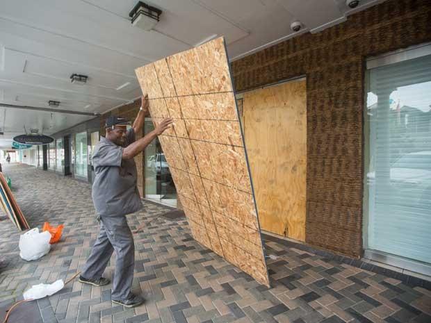 Rapaz protege com placas de madeira uma loja nas Bahamas (Foto: Tim Aylen / AP Photo)
