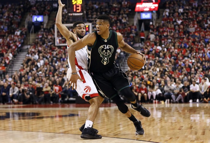 Giannis Antetokounmpo, do Milwaukee Bucks, passa pela marcação de Cory Joseph, do Toronto Raptors (Foto: Reuters/John E. Sokolowski-USA TODAY Sports)