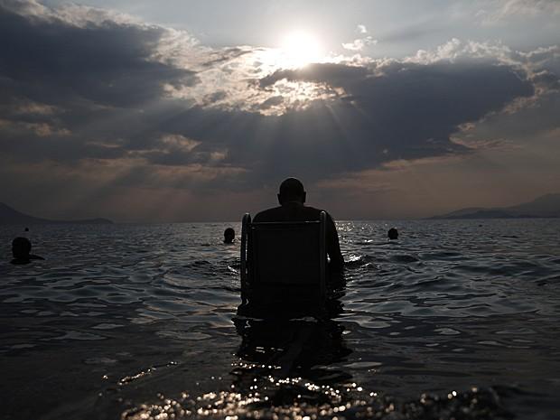 """Lefteris Theofilou, de 52 anos, que sofre de paraplegia, entra no mar com a ajuda do """"Seatrac"""", dispositivo movido a energia solar que permite pessoas com deficiência entrem e saiam do mar de forma autônoma, em praia de Alepochori, no oeste de Atenas, no dia 12 de julho  (Foto: Yorgos Karahalis/Reuters)"""