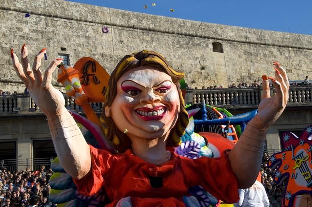 """Um """"maskeruni"""" desfila pela Praça da Liberdade, ponto central do carnaval. Ao fundo, as paredes do forte Cavalier St. James, construídas há mais de 400 anos (Foto: Haroldo Castro/ÉPOCA)"""