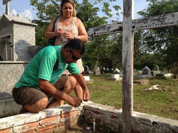 Virgílio Siqueira e Luiza Siqueira visitam o túmulo da avó, pai e mãe, enterrados no cemitério Santo Antônio (Foto: Rosiane Vargas/G1)