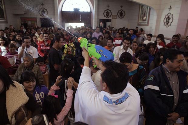 Padre mexicano benze fiéis com pistola de brinquedo (Foto: Daniel Becerril/Reuters)