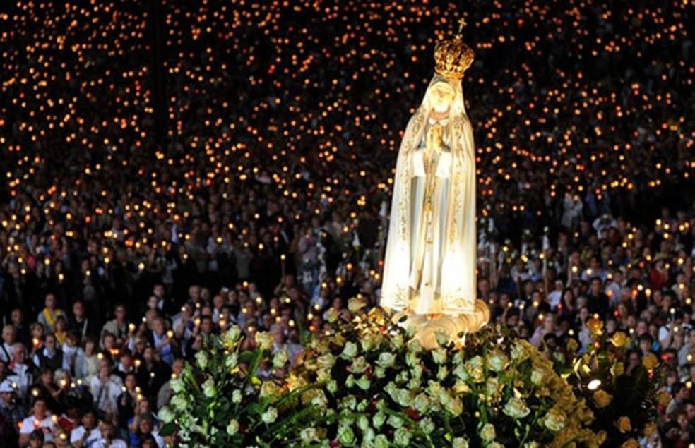 Fiéis carregam imagem de Nossa Senhora de Fátima em procissão em Fátima, Portugal, na noite desta quinta-feira (12). Centenas de peregrinos celebraram o aniversário do milagre de Fátima, em que três crianças pastora afirmaram ter visto a virgem, em 1917. (Foto: AFP)