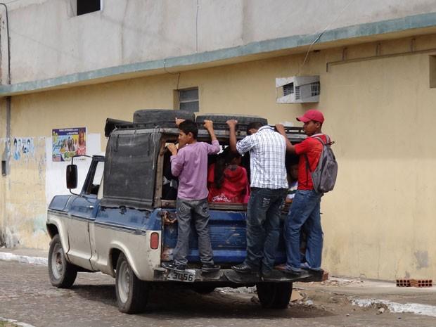Jovens da Zona Rural se arriscam pendurados na traseira da caminhonete (Foto: Luna Markman/ G1)
