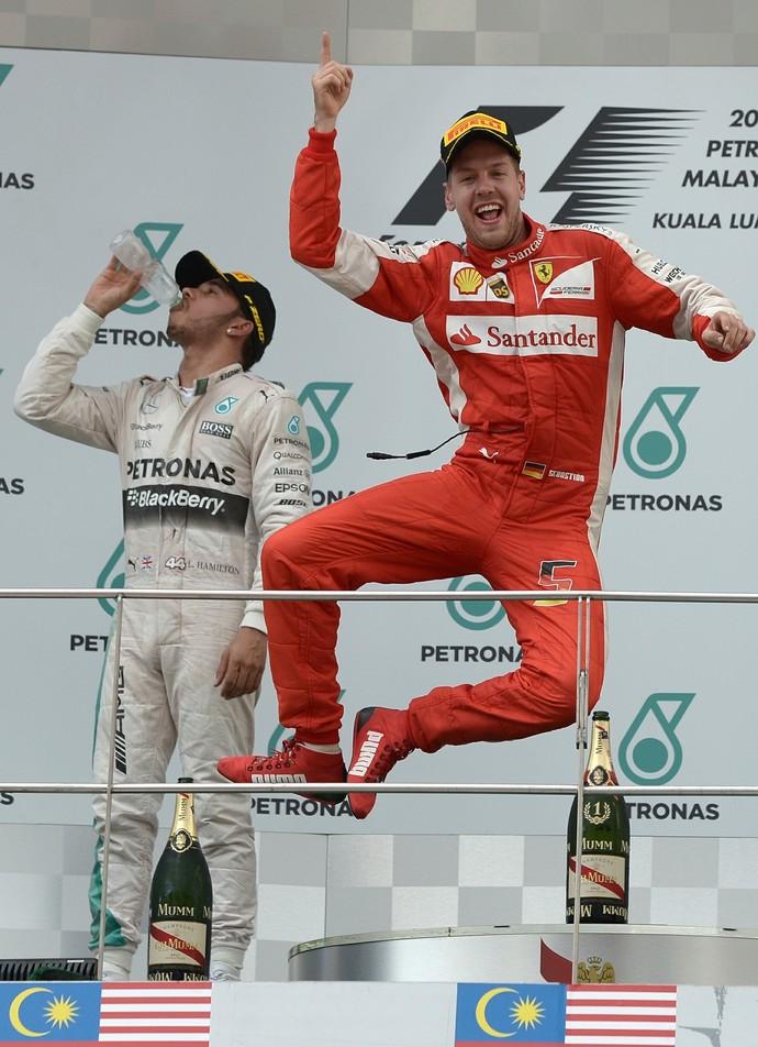 No pódio, Sebastian Vettel bate calcanhares para celebrar vitória no GP da Malásia (Foto: AFP)