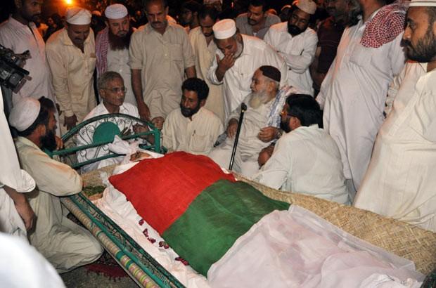 Parentes e partidários de Fakhrul Islam velam o corpo dele nesta quinta-feira (11) na cidade paquistanesa de Hyderabad (Foto: AFP)