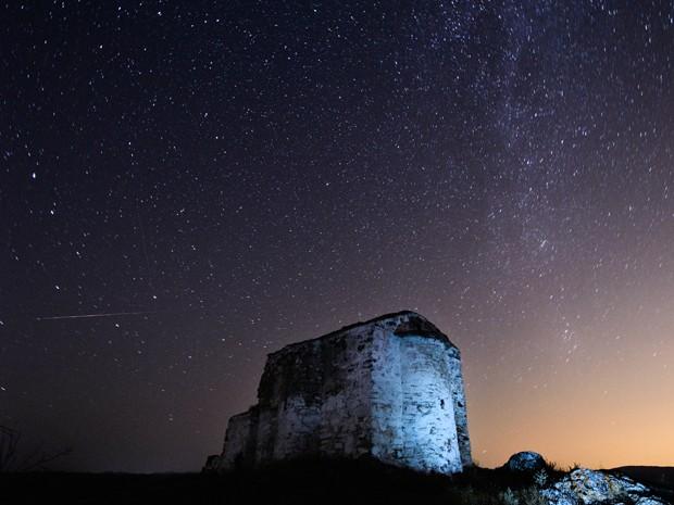 Meteoro Perseida cruza o céu de Potsurnentsi, na Bulgária (Foto: Dimitar Dilkoff/AFP)
