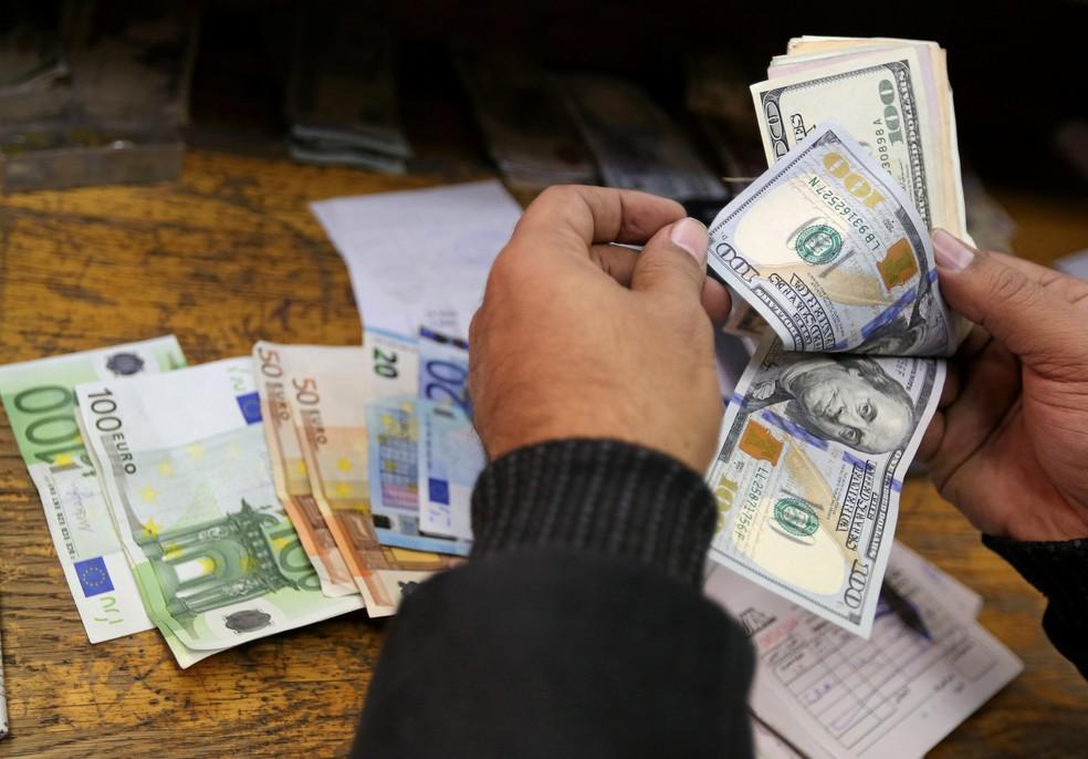 Homem conta notas de dólar e euro. (Foto: Reuters)