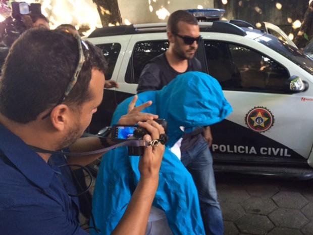 O menor com a cabeça coberta por um capuz ao chegar à DH de tarde, apois sair com os policiais (Foto: Káthia Mello/G1)
