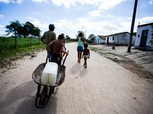 Mãe e filho voltam para casa sem a água. (Foto: Jonathan Lins/G1)