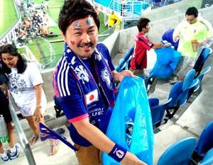À frente, o orgulho da civilidade. Ao fundo, japonês pede a outro torcedor para jogar o lixo no saco (Foto: Chandy Teixeira/GloboEsporte.com)