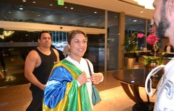 Sorridente e com bandeira do Brasil, Bethe Correia chega ao Rio de Janeiro