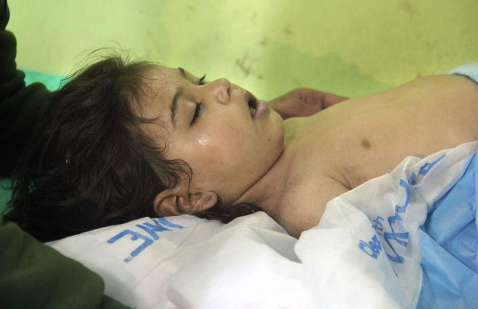Criança inconsciente é mantida sob observação em hospital de Khan Sheikhoun, na Síria, após suposto ataque com gás tóxico em área tomada por rebeldes (Foto: Omar Haj Kadour/AFP)