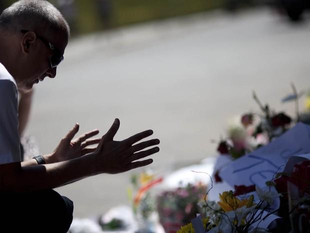 Homem ora durante homenagem em memorial na boate Kiss (Foto: Felipe Dana/AP)