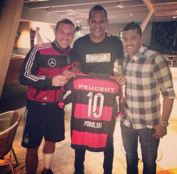 Podolski com André Santos mostra camisa do Flamengo (Foto: Reprodução)