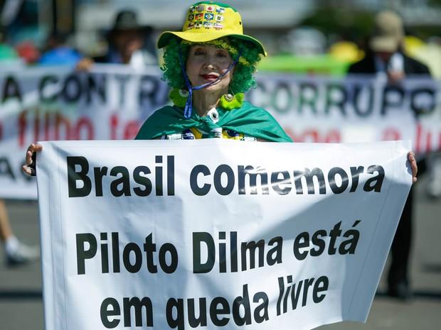Mulher exibe faixa de protesto em Brasília (Foto: Evaristo Sá/AFP)