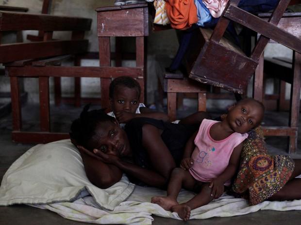 Uma mulher descansa ao lado de seus filhos no chão de um abrigo em Les Cayes, no Haiti, antes da passagem do furacão Mateus (Foto: Andres Martinez Casares/Reuters)