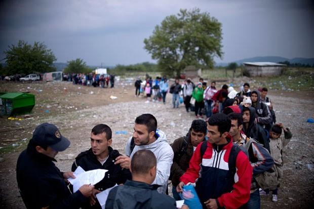 Migrantes e refugiados fazem fila para se registrar em um campo após atravessarem a fronteira entre Grécia e Macedônia nesta terça-feira (22) (Foto: Nikolay Doychinov/AFP)