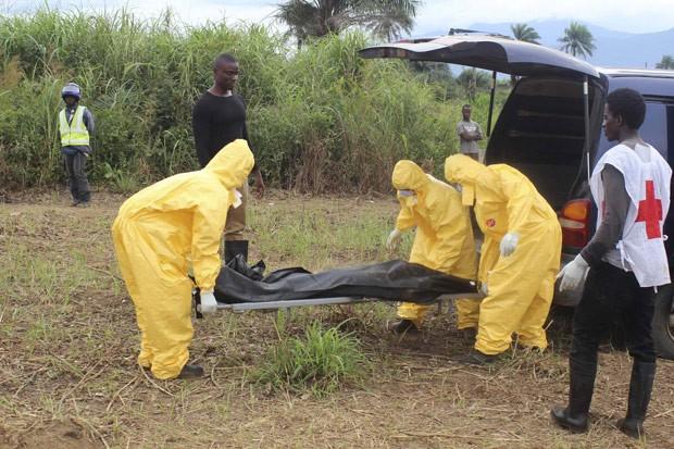 Profissionais da saúde carregam corpo de uma pessoa que morreu com ebola em Freetown, capital de Serra Leoa, nesta quarta-feira (21) (Foto: Reuters/Josephus Olu-Mamma)