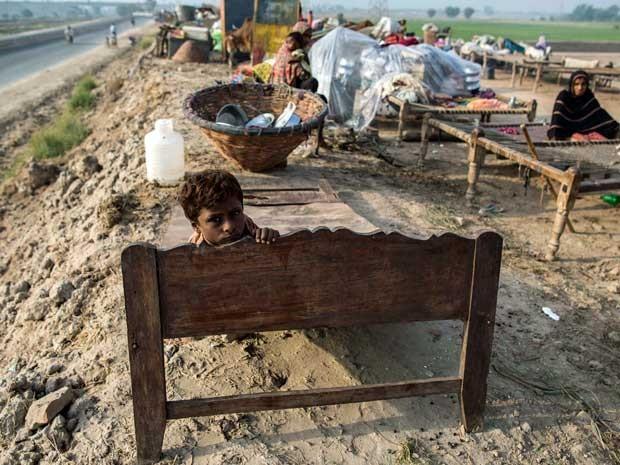 Afetado pelas inundações guarda poucos pertences e aguarda ajuda para deixar região inundada. (Foto: Zohra Bensemra / Reuters)