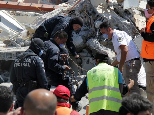 Equipes trabalham no resgate às vítimas presas entre os escombros de um shopping no México (Foto: STR/AFP)