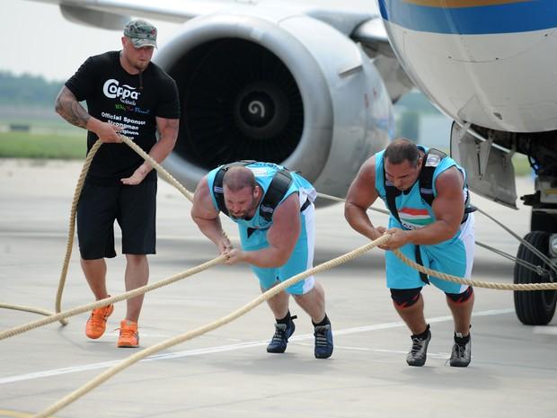 Equipe tenta arrastar avião de 34,5 toneladas durante competição do força (Foto: AFP)