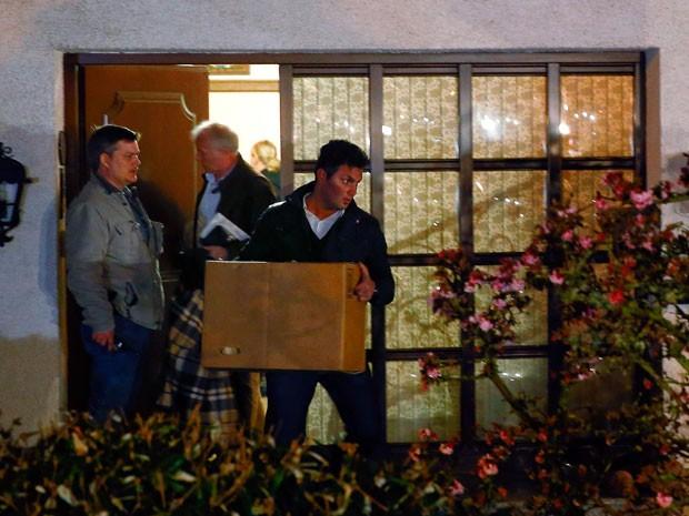 Policial deixa casa do copiloto Andreas Lubitz em Montabaur, na Alemanha, carregando objetos pessoais dele (Foto: Kai Pfaffenbach/Reuters)