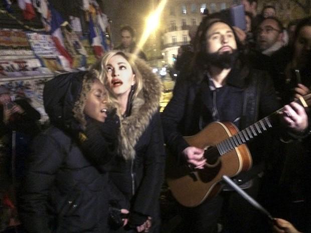 Madonna canta na Praça da República, em Paris, ao lado do guitarrista Monte Pittman e do filho dela David Panda (Foto: Jules Mahe/AFP )